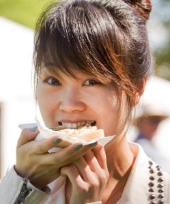 Mia Zhao chows down on a whitebait patty during the Great West Coast Whitebait Festival. (source of photo)